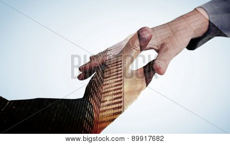 Businesspeople going to shake hands against low angle view of skyscrapers