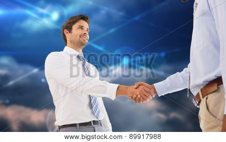 Young businessmen shaking hands in office against lines against glowing sky