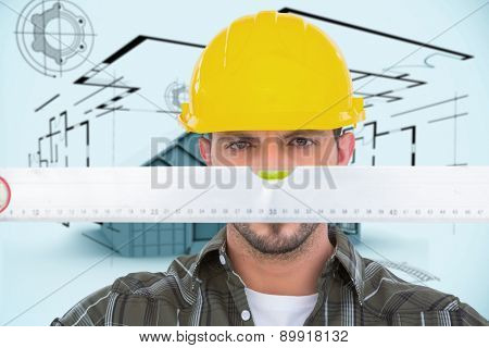 Handyman looking at spirit level against architecture plan with house