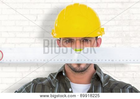 Handyman looking at spirit level against white wall