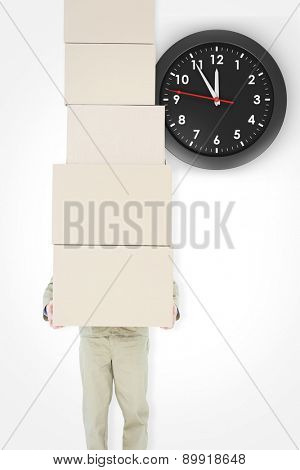 Delivery man carrying stacked boxes against clock