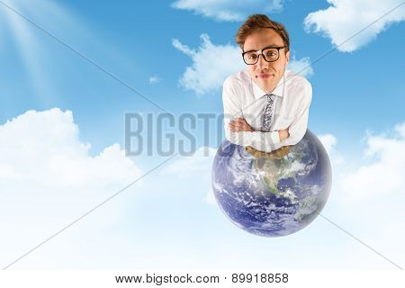 Young geeky businessman looking at camera against blue sky