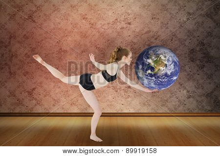 Side view of a sporty young woman standing on one leg against grimy room