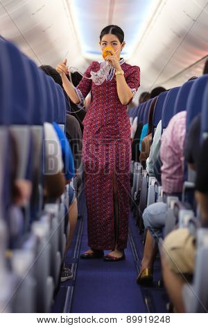 BANGKOK, THAILAND, DECEMBER 29, 2014 : An air hostess of the Thai Lion Air company is showing how to use oxygen mask before taking off from the Suvarnabhum airport in Bangkok, Thailand