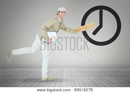 Happy delivery man running while holding parcel against grey room
