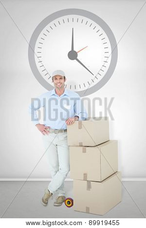 Confident delivery man leaning on stacked cardboard boxes against grey room