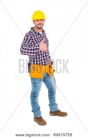 Smiling handyman gesturing thumbs up on white background
