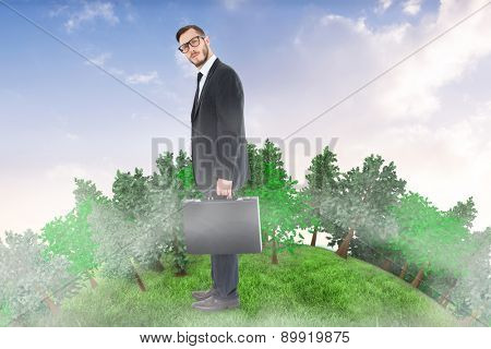 Geeky businessman holding his briefcase against beautiful orange and blue sky