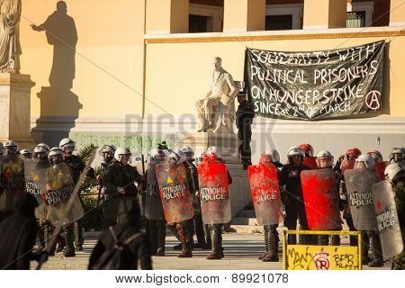 ATHENS, GREECE - APR 16, 2015: Riot police with their shield, take cover during a rally in front of Athens University, which is under occupation by protesters leftist and anarchist groups.