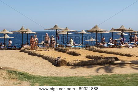 Group Of Elderly People Playing Bocce On The Beach.