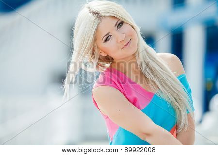 Stylish beautiful girl sitting on the stairs in bright clothes