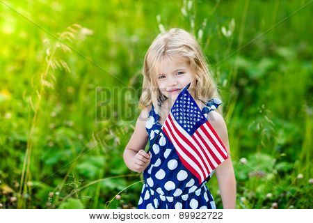 Cute Smiling Little Girl With Long Curly Blond Hair Holding An American Flag On Sunny Day In Summer