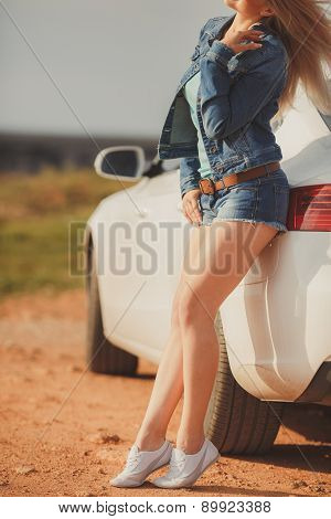 Slender beautiful woman posing next to a beautiful car.