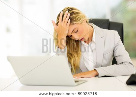 stressed businesswoman having headache at work