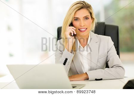 beautiful young businesswoman talking on landline phone