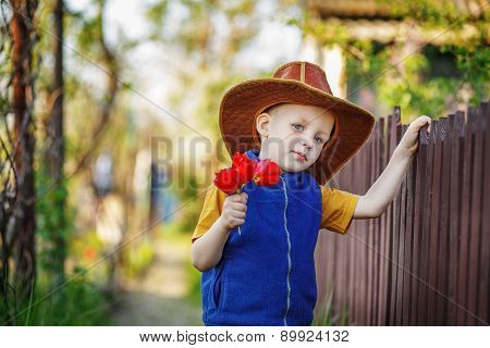 Portrait Of A Little Boy Standing In A Big Hat With A Bouquet Of Tulips At The Wooden Fence