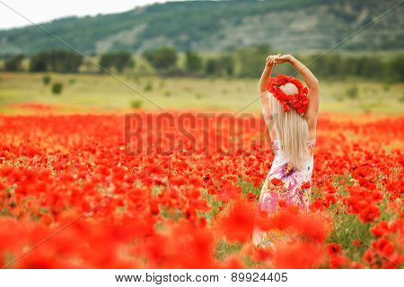 Young beautiful girl in a field of blooming poppies.
