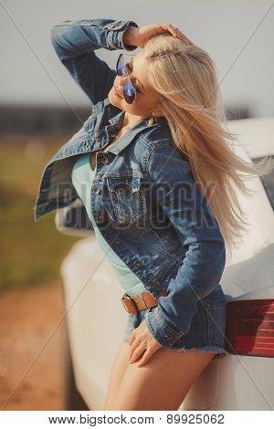 Slender beautiful woman posing next to a beautiful car.