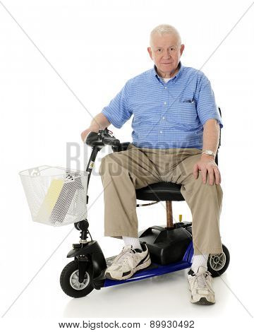 A senior man happily looking at the viewer from his electric scooter.  On a white background.