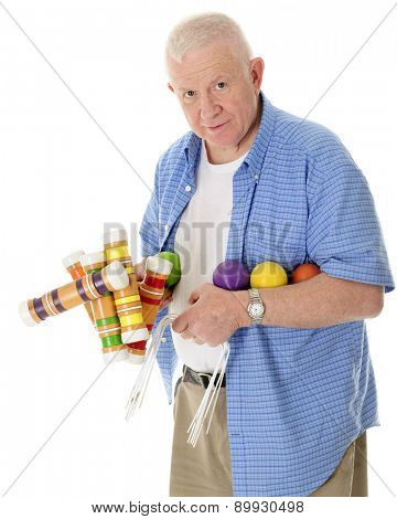 A casual senior adult man looking at the viewer carrying a load of croquet mallets, balls and wickets.  On a white background.