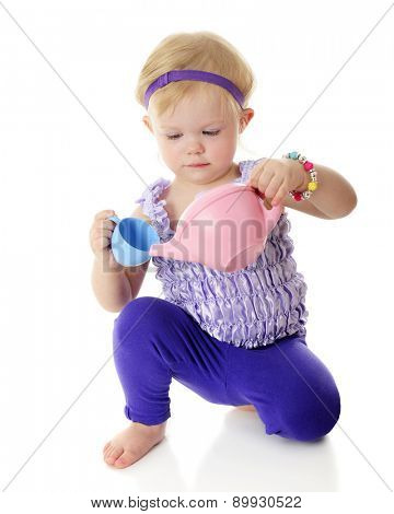 An adorable 2-year-old pretending to pour tea with her pastel tea set.  On a white background.