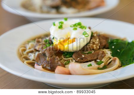 Udon noodles topped with meat and poached egg