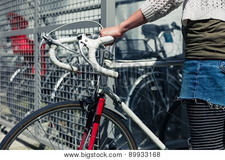 Young Woman Getting Her Bike Out Of A Bicycle Shed