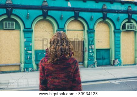 Woman Looking At Boarded Up Building