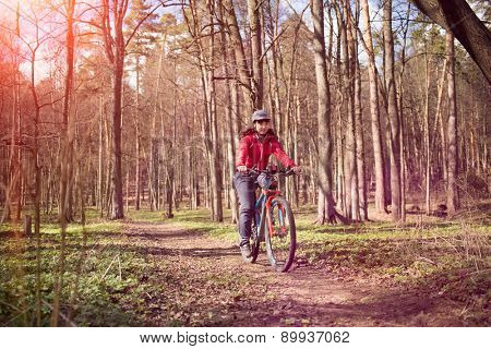Young attractive woman riding a bicycle through forest