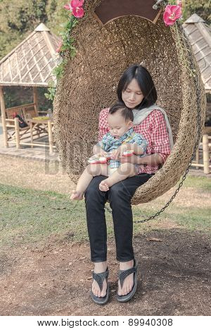 Mother hug baby on the rattan swing