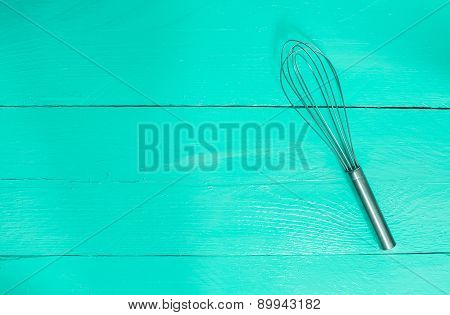 Whisk On Turquoise Wood As Background