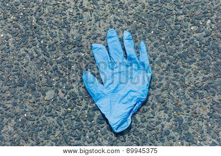 Blue Latex Glove On The Ground Outside