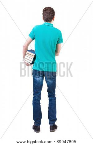 A man carries a heavy pile of books. back view.  backside view of person.  Isolated over white background. Clutching a stack of books under his arm man standing and looking into the distance.