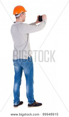 Backview of an engineer in construction helmet stands and enjoys tablet or using a mobile phone. backside view of person.  Isolated over white background. A worker in a helmet photographs tablet.