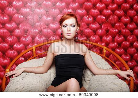 Young woman in black lingerie sitting on chair