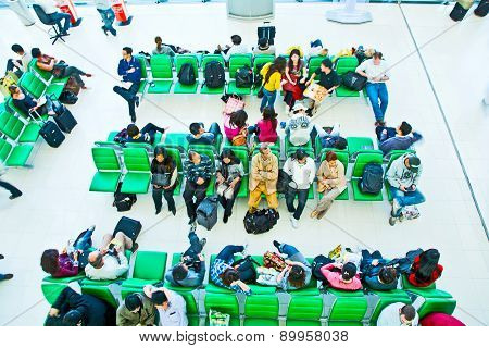 People Wait On Benches For The Departure Of Their Flight At Suvarnabhumi International Airport