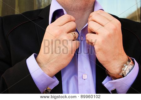 A man in a business suit straightens his shirt