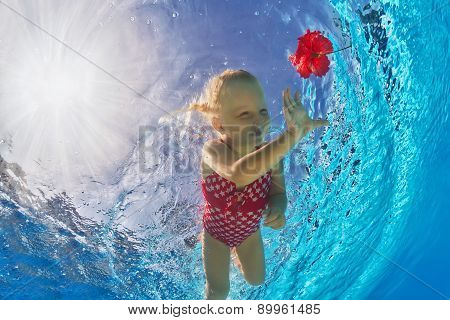 Cute Girl Diving Underwater In The Pool For A Red Flower