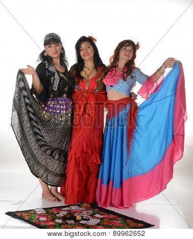 Three gypsy women posing in traditional outfits