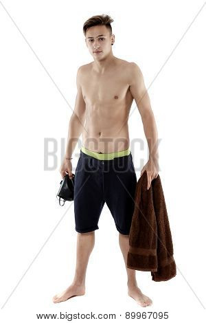 Young attractive caucasian man swimmer with goggles and towel isolated over white background