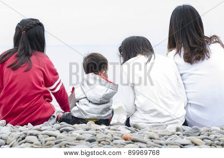 Summer vacation family four people watching the sea