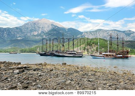 Sailing ships in the bay against background mountains
