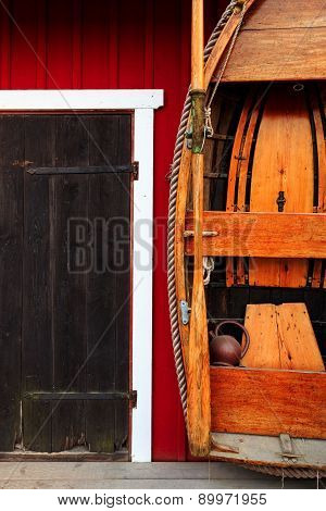 Red fishing hut with black door and wooden row boat