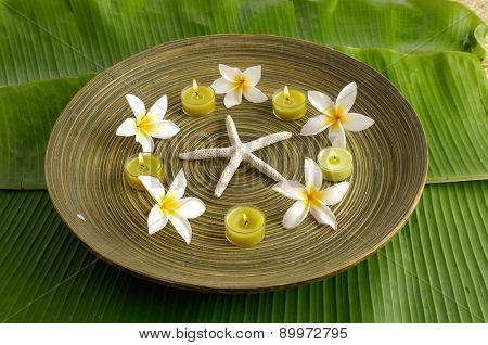 Five gardenia flower with candle in wooden bowl ,starfish on banana leaf texture
