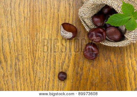 Chestnuts In Burlap On Wood Textured.useful As Background