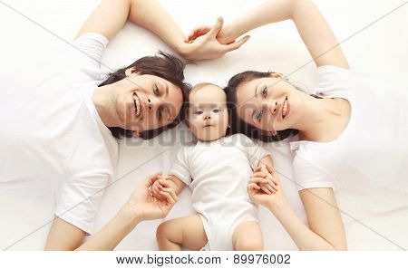 Closeup Portrait Of Happy Family Together Lying On The Bed At Home, Top View