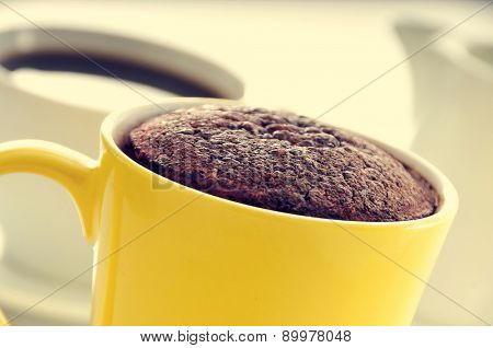 closeup of a chocolate mug cake in a yellow porcelain mug and a cup of coffee