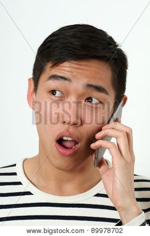 Astonished young Asian man using a smartphone.