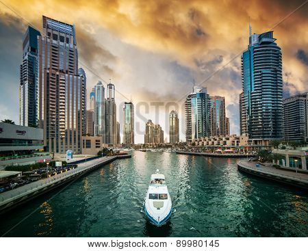 Dubai, United Arab Emirates - December 14, 2013: Modern skyscrapers and water channel with boats of Dubai Marina at sunset, United Arab Emirates