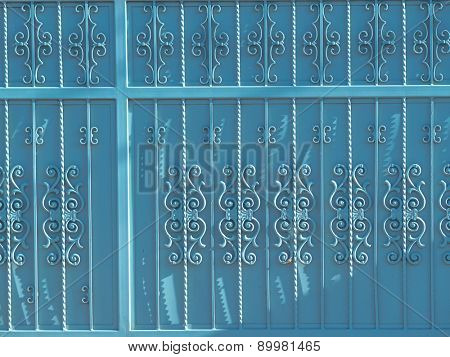 Ornate metal gate background, painted blue.